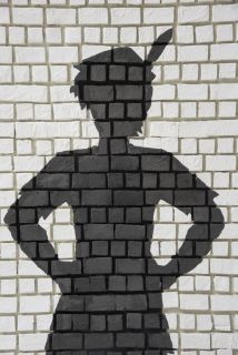 43467572 - painted silhouette peter pan on white brick wall